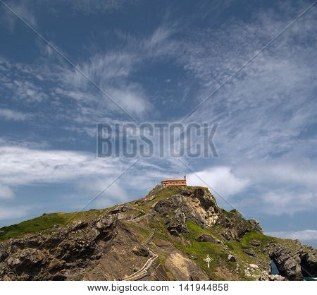 Chapel at rock top on an ocean coast. A chapel Doniene Gaztelugatxeko chapel (San Juan - Gastelugache) in the Basque Country northern Spain in the sunny summer day against the blue sky with plumose clouds