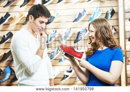 female sale assistant demonstrates shoe to man at footwear shop