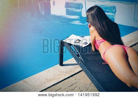 Woman lying on deckchair and reading magazine near swim pool outdoors