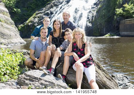 A family in front of a waterfall having great time