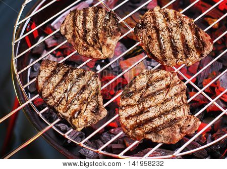 Pieces of sirloin are grilling on the barbecue.