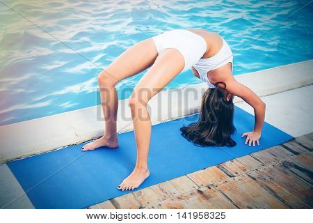 Portrait of a young woman doing yoga bridge pose outdoors