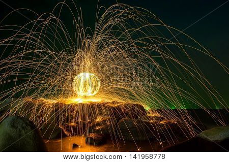 Hot Golden Sparks Flying From Man Spinning Burning Steel Wool Into A Sphere On A Rocky Shoreline., L