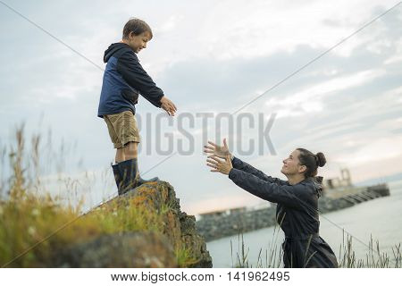 A mother Helping Children To Jump Off Rocks