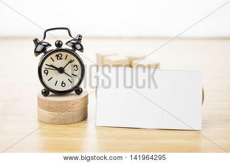Blank Business Card Mock Up And Black Alarm Clock On Light Wooden Table, Business Corporate Identity