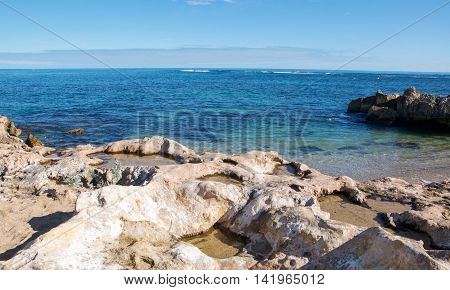 Limestone rock pools and the turquoise Indian Ocean seascape under a blue sky at Point Peron in Rockingham, Western Australia