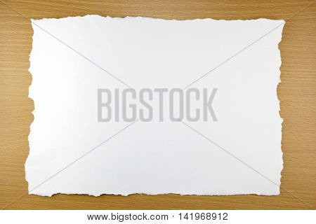 white paper tear on brown wood background and you can input text in copy space.