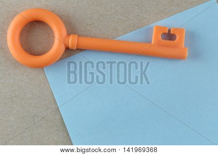 Orange Plastic key is placed on Blue Paper Note and can input text to it.