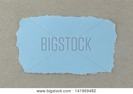 Blue paper tear on brown cardboard background and you can input text in copy space.