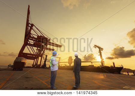 foreman control loading Industrial Container Cargo freight ship from his manager with working crane bridge in shipyard for import export logistics.