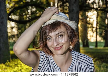 Young caucasian woman with stylish sunhat posing in the forest. Sunny backlight. Sexy female portrait. Beauty fashion and nature. Positive emotions. Smiling face.