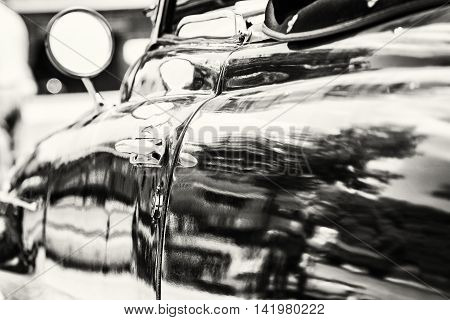 Close up photo of veteran car with rear-view mirror and handle. Vintage car. Old automobile. Black and white photo.