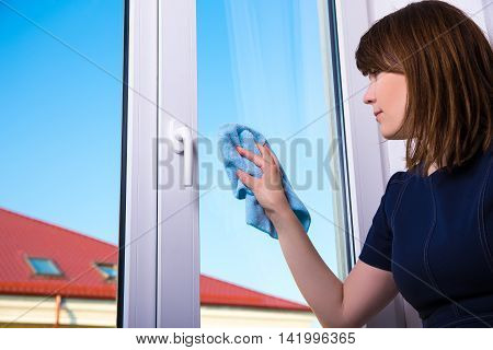 housework concept - woman cleaning window with special rag at home
