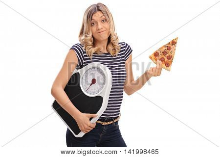 Tempted young woman holding a slice of pizza in one hand and a weight scale in the other isolated on white background