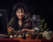 Middle-aged female fortuneteller works on-line with semi-precocious gemstones. Black haired diviner sits at the desk surrounded by different jasper spheres, smoking candles. She holds some gemstones in hands and looks at the monitor. Horizontal indoors sh poster