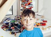little cute preschooler boy playing lego toys at home happy smiling, lifestyle real children concept poster