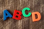 ABCD spelling from plastic letters on wooden background poster