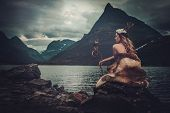 Nordic goddess in ritual garment with hawk near wild mountain lake in Innerdalen valley, Norway. poster