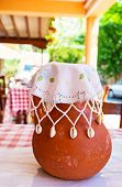 The crock with wine covered with the handmade napkin decorated with lace embroidery and seashells Gourri village Cyprus. poster