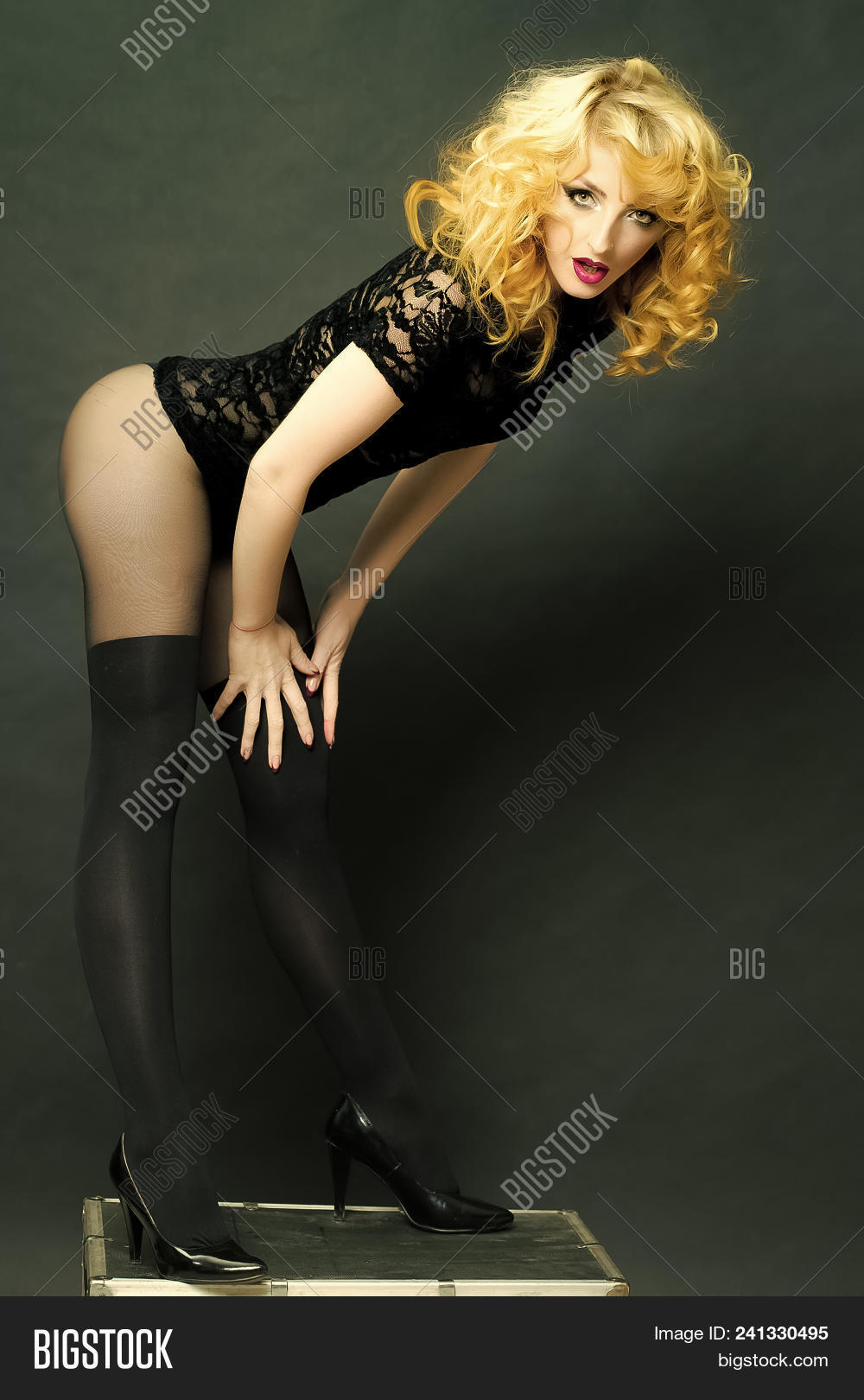 59dbc602348b High fashion portrait of elegant woman. Sensual woman. Sexy blonde young woman  with curly hair in black lace dress underwear shoes and stocking standing in  ...