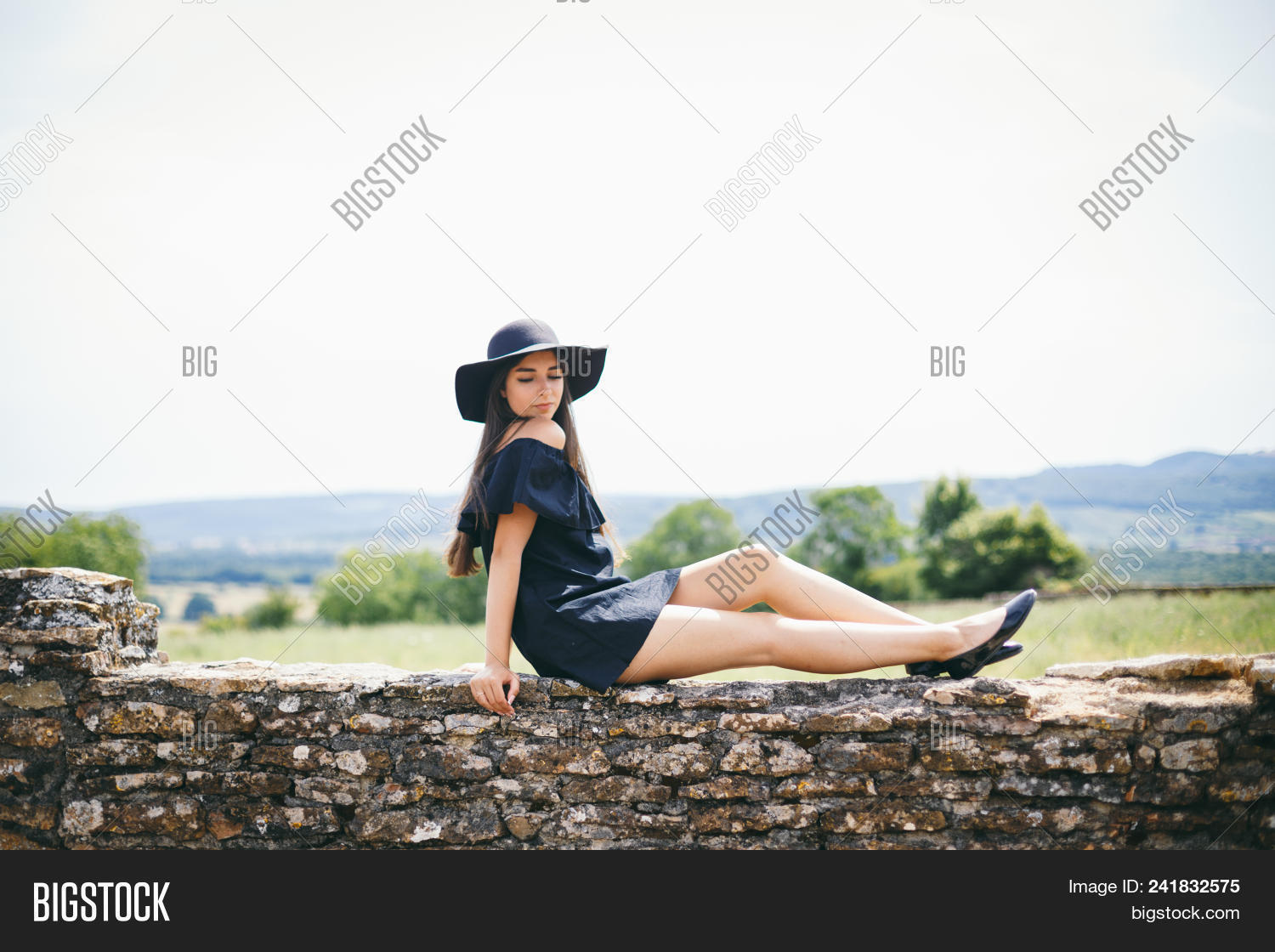 c3a986a4370 beautiful young, sexy woman model of brunette with dark skin black short  dress and hat with fields, fashionably dressed sits in French village in  burgundy ...