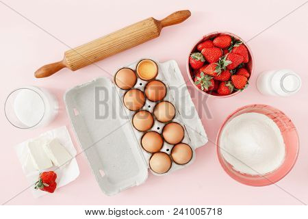 Flat Lay Raw Ingredients For Cooking Strawberry Pie Or Cake On Pink Background  (eggs, Flour, Milk,