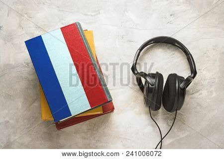 Headphones And A Pile Of Book. The Upper Book Has A Cover In The Form Of A Flag Of France. Concept A