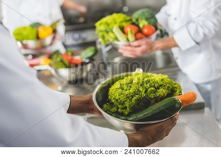 Cropped Image Of Multicultural Chefs Holding Bowls With Vegetables At Restaurant Kitchen
