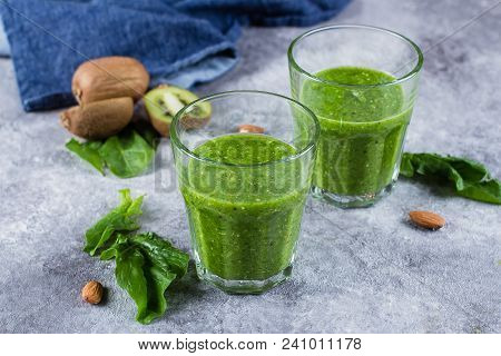 Helathy Green Smoothie With Green Apple, Spinach, Kiwi And Almond Nuts On Gray Concrete Background.
