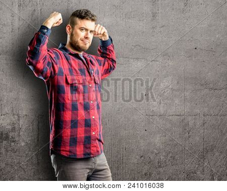 Young handsome man pointing biceps expressing strength and gym concept, healthy life its good