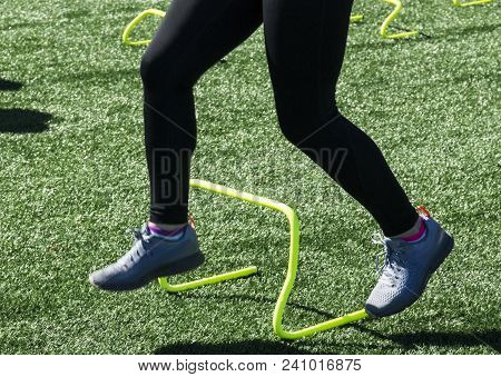 A High School Track And Field Athlete Is Running Over Yellow Mini Banana Hurdles During Strenght And