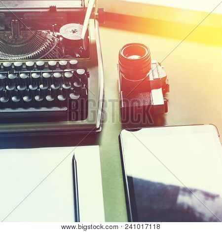 Analog Typewriter, Digital Tablet And Film Camera On The Green Table, Top View With Sunshine. Journa