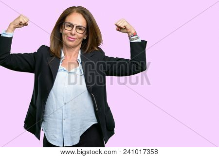 Middle age business woman showing biceps expressing strength and gym concept, healthy life its good