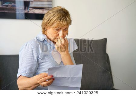 An Elderly Woman Reads Negative News In A Letter At Home On The Couch. An Elderly Woman Received A N