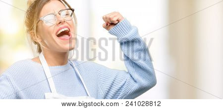 Young woman shop owner, wearing apron happy and excited celebrating victory expressing big success, power, energy and positive emotions. Celebrates new job joyful
