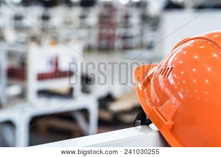 Orange Protective Helmet Or Hard Hat Against Industrial Background At Machinery Plant. Headpiece As