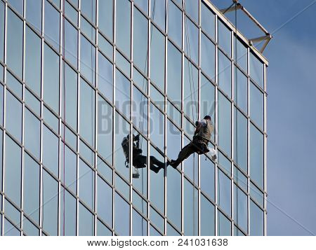 Worker On A Glass Facade Of Office Building. Windows Cleaner On Skyscraper Wall
