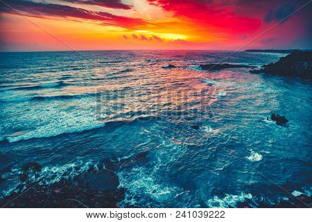 Spectacular bright sunset over the Indian ocean next to Galle, Sri Lanka. Stunning seascape. The contrast combination of red, orange and blue colors. Beauty of wild nature.