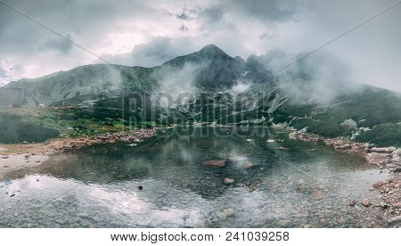 The fairy tale misty landscape the mountain Kalnate pleso lake surrounded by the mighty Tatras. Tatranska Lomnica, Slovakia. Ideal background in grey shades for the collages and illustrations.