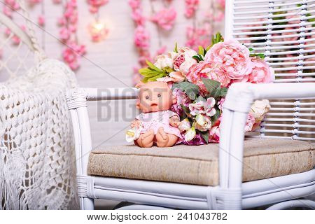 Toy Easter, Painting Eggs On A Wooden Bench In Front Of A Wooden Wall Beside A Flowering Plant.