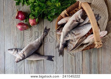 Fish European Bass (dicentrarchus Labrax) In A Wicker Basket, Parsley And Onions   On A Wooden Table
