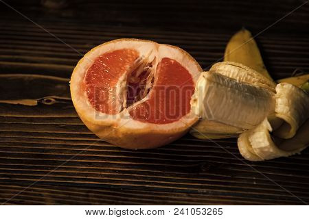 Penis And Vagina, Banana With Yellow Peel In Red Grapefruit On Wooden Background, Sex And Sexual Int