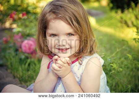 Innocence, purity and youth concept. Future and flourishing. Girl smiling with folded hands in summer garden. Child sitting at blossoming rose flowers on green grass. Germination and growth. poster