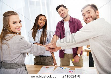 Multicultural Group Of Marketing Managers Holding Hands Together In Office, Teamwork Concept