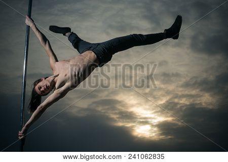 Acrobatic Elements Of Man Dancing On Pole. Acrobatic Elements Of Pole Dancer In Sunset