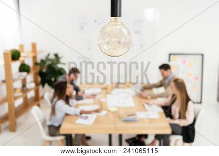 Selective Focus Of Light Bulb And Multicultural Group Of Marketing Managers Working In Office