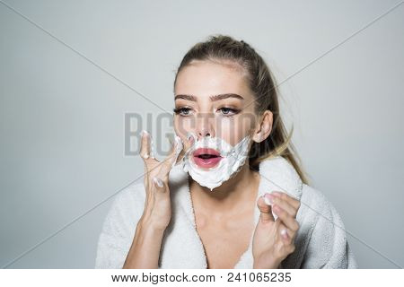 Girl on busy face in bathrobe covering face with foam for shaving, grey background. Woman with face covered with foam. Lady cares about smooth skin. Skin care and shaving concept. poster