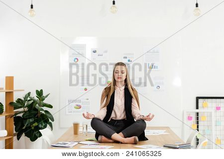 Calm Businesswoman Meditating In Lotus Position On Table In Office