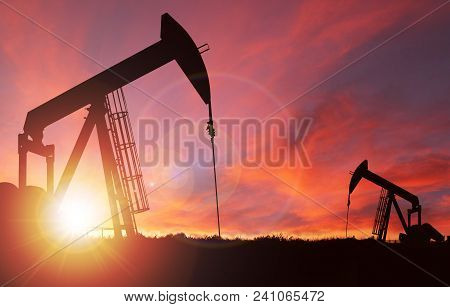 Pump Jack Silhouette Against A Sunset Sky With Deliberate Lens Flare And Copy Space. These Jacks Can