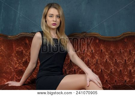 Portrait Of A Stunning Fashionable Model Sitting In A Chair. Business, Elegant Businesswoman. Interi